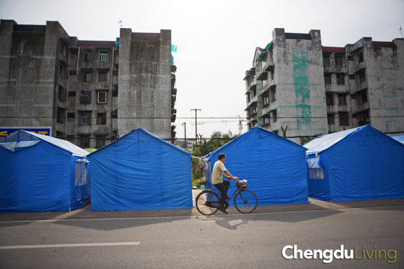 Bicyclist rides past tents